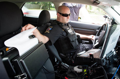Officer Jeff Innocenti pulls a ticket from his printer during a traffic stop for cell phone use.