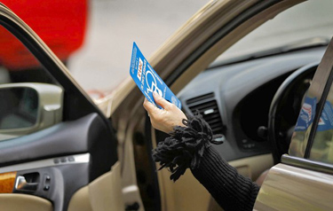 DMV investigators collect a disabled placard from a motorist during a sting in Beverly Hills in April. (Al Seib / Los Angeles Times / April 12, 2011)