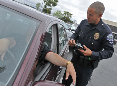 Torrance Police conduct cell phone enforcement operation on drivers along Hawthorne Boulevard. Some critics say state lawmakers are using new traffic laws as a backdoor form of taxation. (Robert Casillas Staff Photographer)