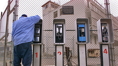An inmate is shown at a bank of prison pay phones in Tracy, Calif. (Los Angeles Times)