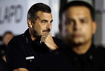LAPD Chief Charlie Beck watches officers assemble Tuesday before they boarded buses at Dodger Stadium. Credit: Mark Boster / Los Angeles Times