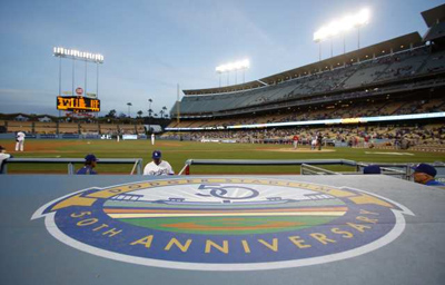 A dugout is adorned with a Dodger Stadium 50th anniversary logo. Credit: Associated Press