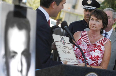 Los Angeles City Councilman Eric Garcetti, left, presents a commemorative plaque to Valerie Campbell-Moniz, right, at the dedication of a Hollywood intersection in honor of her father, LAPD Officer Ian Campbell, who was murdered in a Kern County onion field in 1963. The case was the basis for a bestselling book by Joseph Wambaugh. Campbell-Moniz was 3 at the time of her father's death. (Brian van der Brug / Los Angeles times / August 11, 2012)