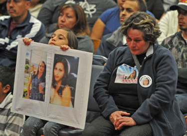 Maria Christina Perez, mother of recent murder victim Cristy Alvarez, listens to speakers at the Wilmington meeting as her daughter Katharine Alvarez, 7, holds photos of her sister. (Robert Casillas / Staff Photographer)