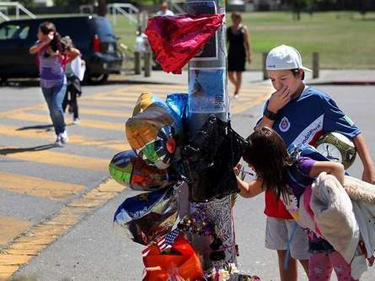 "Armando Jimenez, 13, and his sister, Ashley Jimenez, 7, stop to look at the memorial site for 4-year-old Christopher ""Buddy"" Rowe.Christopher Chung / PD"