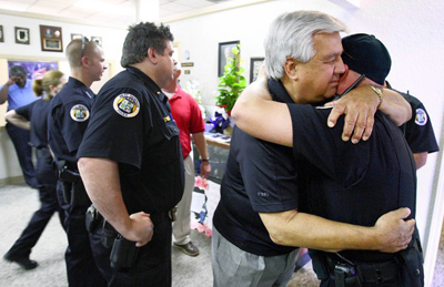 Bob Paudert, then chief of the West Memphis police force, is comforted by an officer after his son was killed while making a routine traffic stop in 2010. The shootout that ensued involved a member of the sovereign citizens movement. (Mike Brown, The Commercial Appeal / May 24, 2010)