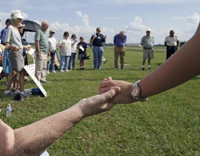 Death penalty opponents join hands and pray Wednesday moments before the scheduled execution of Manuel Valle outside Florida State Prison. Valle was convicted of killing a Coral Gables police officer 33 years ago. Credit: John Raoux / Associated Press
