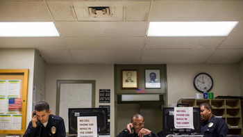 LAPD officers answer phones in the lobby of the Southeast Community Police Station, which has been found to have black mold on the ceiling HVAC vents. (Gina Ferazzi / Los Angeles Times)