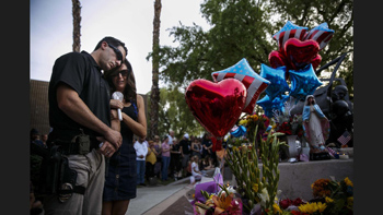 Palm Springs Police Sgt. Kyle Stjerne is embraced by Brooke Stjerne as he mourns the loss of his co-workers during a vigil. <i>Los Angeles Times</i>